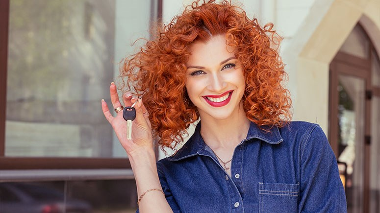 Red head young woman holding car keys while smiling